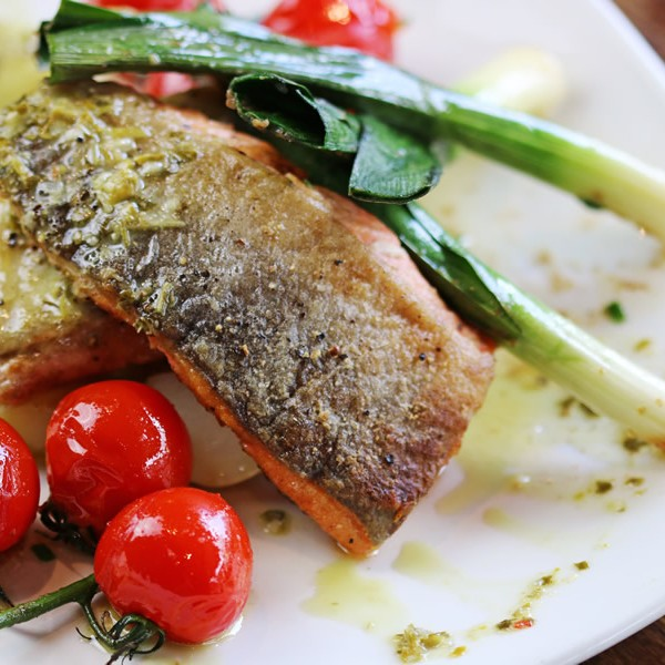Roasted sea trout, baby leeks & roasted vine tomatoes, with crushed new potatoes, lime & spring onion salsa verde